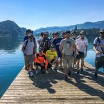group of cyclists on the shore of lake bled
