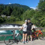 happy cyclists and alpine river