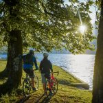gravel cyclists enjoying the view on lake bohinj